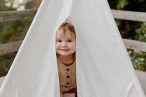 Happy child peeking from tent