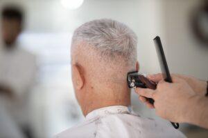 back of man's head receiving a haircut